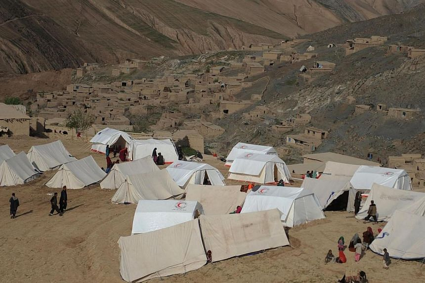 Landslide-affected Afghan villagers are pictured at their relief tents near the scene of the incident in Argo district in Badakhshan on May 4, 2014. -- PHOTO: AFP