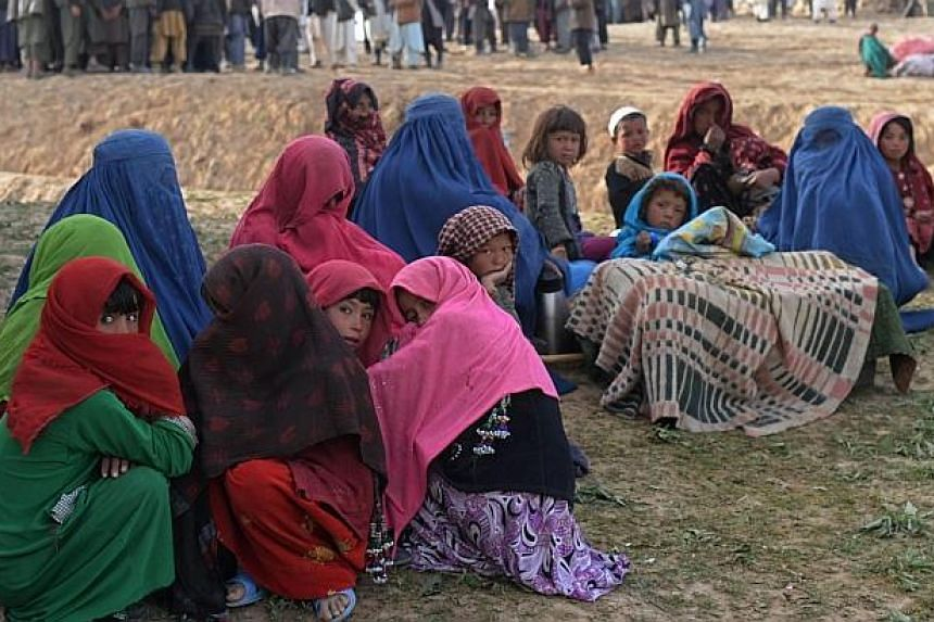 Landslide-affected Afghan villagers look on as they await donated relief supplies at the scene of the incident in Argo district in Badakhshan on May 4, 2014. -- PHOTO: AFP