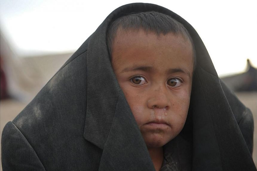 An Afghan boy looks on he stands at the site of a landslide at the Argo district in Badakhshan on May 3, 2014. -- PHOTO: AFP