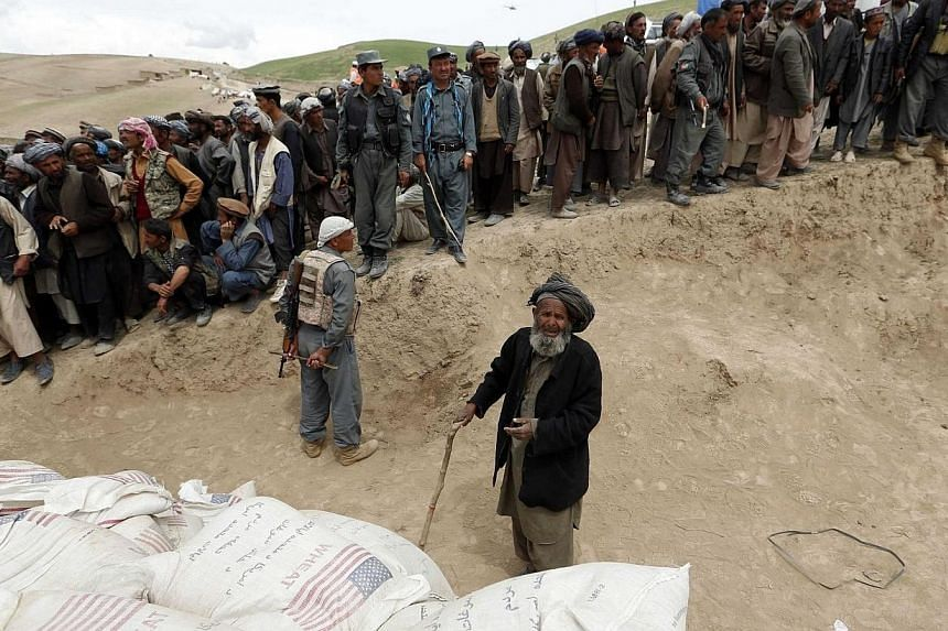 Afghan survivors wait for aid near the site of a landslide at the Argo district in Badakhshan province on May 4, 2014. Aid groups on Sunday, May 4, 2014, rushed to reach survivors of a landslide in northern Afghanistan that entombed a villa