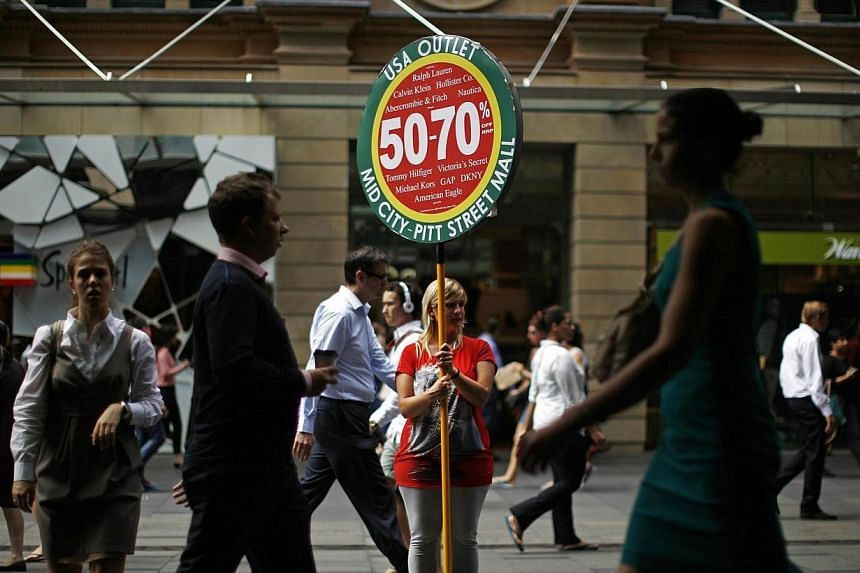 "A retail worker holds up an outlet store promotion in downtown Sydney on March 6, 2014. The Australian budget later this month will involve ""tough decisions"" to put the economy back on track, a senior minister said on Sunday, May 4, 2014, as a p"
