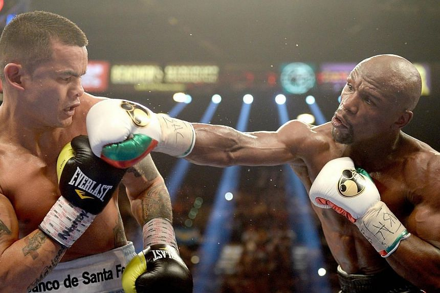(From right) Floyd Mayweather Jr. knocks back Marcos Maidana during their WBC/WBA welterweight unification fight at the MGM Grand Garden Arena on May 3, 2014 in Las Vegas, Nevada. Undefeated welterweight Floyd Mayweather did all his hard work in