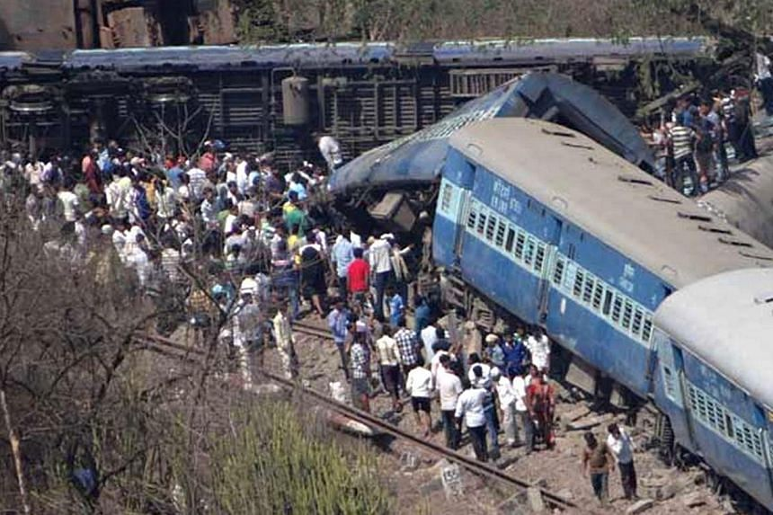 A crowd is pictured near mangled train coaches near Nidi village after the train derailed in Raigad district of India's Maharashtra state on May 4, 2014. A passenger train derailed in western India on Sunday, May 4, 2014, killing at least 18 peo