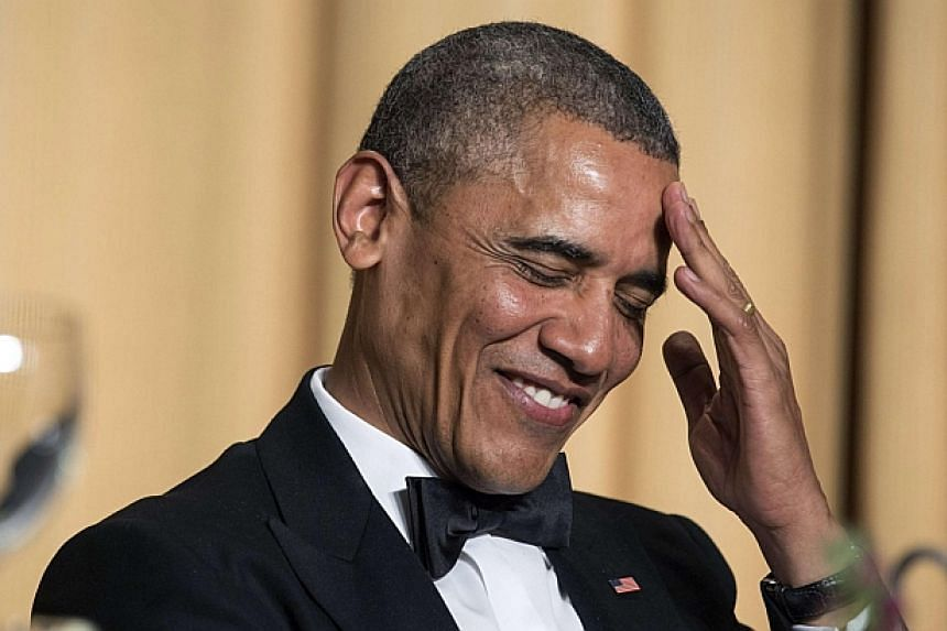 US President Barack Obama rubs his head as he laughs at a joke during the White House Correspondents' Association Dinner in Washington on May 3, 2014. -- PHOTO: REUTERS