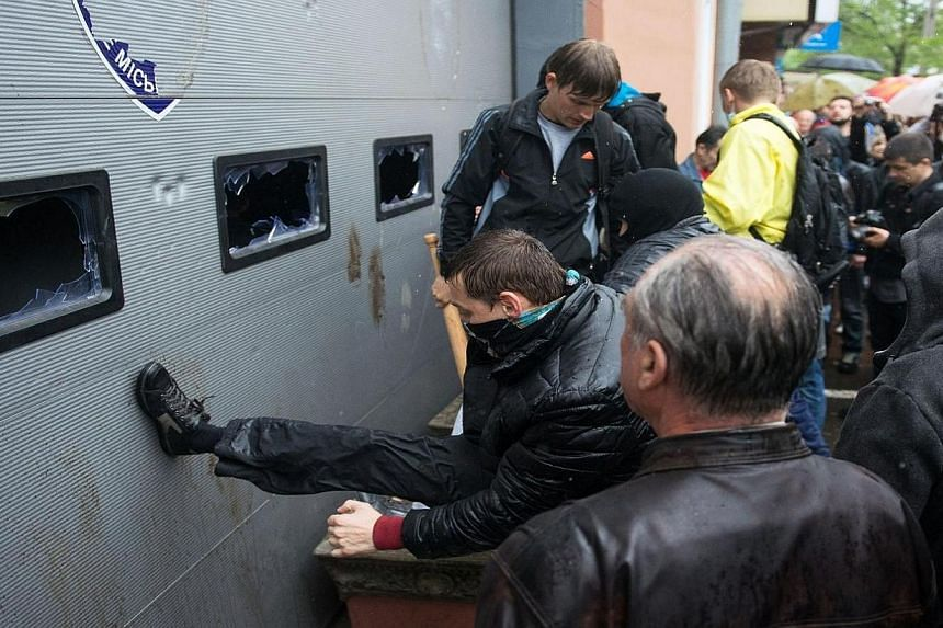 Pro-Russian militants storm the police station in the southern Ukrainian city of Odessa on May 4, 2014, to free the Pro-Russian activists arrested on May 2 after their attack of a Ukrainian unity rally. Thousands of pro-Russian protesters assaul