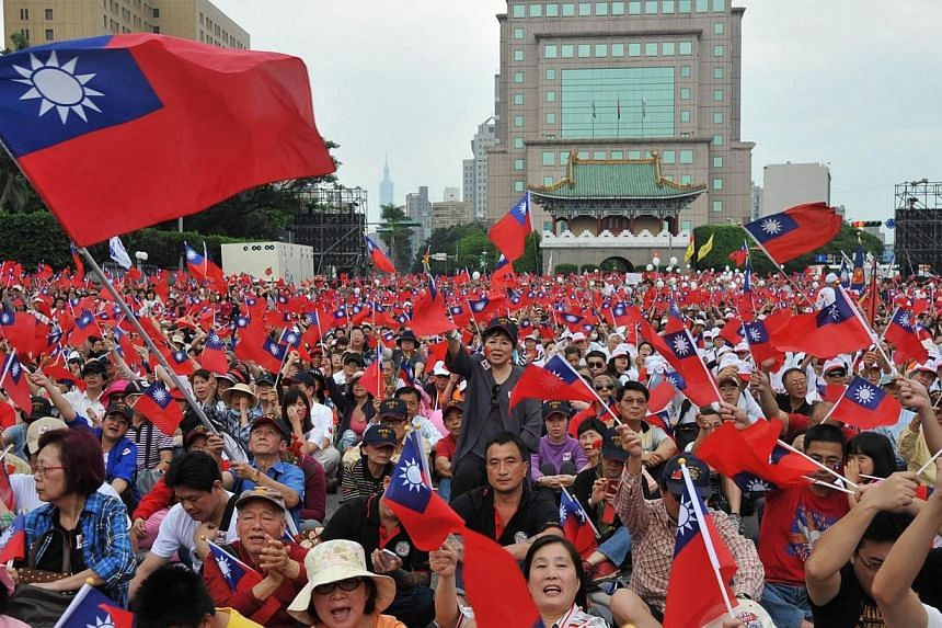 People wave Taiwan flags and chant slogans during a rally near the Presidential Palace in Taipei on May 4, 2014.Thousands of Taiwanese calling for peace and the rule of law rallied in Taipei on Sunday,May 4, 2014, to counter a recent seri