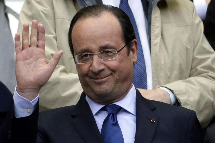 French President Francois Hollande waves prior to the French Cup final football match between Rennes (SRFC) and Guingamp (EAG) on May 3, 2014 at the Stade de France in Saint-Denis, north of Paris. French President Francois Hollande told a Sunday