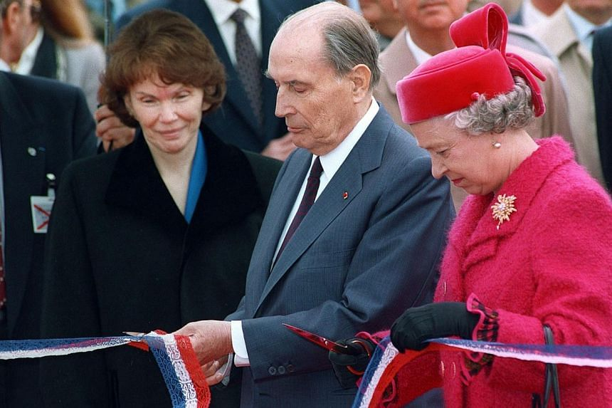 In a file picture taken on May 6, 1994 French President François Mitterrand (second from right) and Britain's Queen Elizabeth II (right) cut a ribbon as Mr Mitterand's wife Danielle (left) looks on at the inauguration of the Channel Tunnel in Coqull