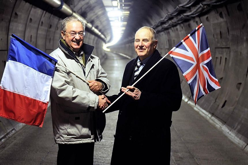 A file picture taken on Feb 10, 2014 shows former workers holding their national flags, French man Philippe Cozette (right) and British man Graham Fagg, who dug the last meters of the Eurotunnel before the junction, posing in the maintenance tunnel n