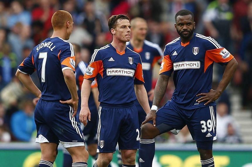 Fulham players (from left-right) Steve Sidwell, Scott Parker and Darren Bent react during their English Premier League football match against Stoke City at the Britannia stadium in Stoke, May 3, 2014. Fulham and Cardiff City were relegated from the P
