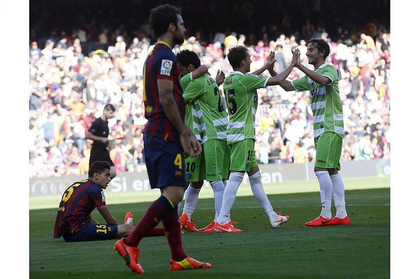Getafe's players celebrate a goal against Barcelonas as Cesc Fabregas (front) walks by during their La Liga match at Camp Nou stadium in Barcelona on May 3, 2014. -- PHOTO: REUTERS