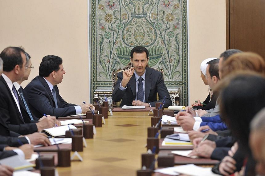Syria's President Bashar al-Assad (centre) meets with members of the Higher Committee for Relief in Damascus May 3, 2014, in this handout released by Syria's national news agency SANA. -- PHOTO: REUTERS