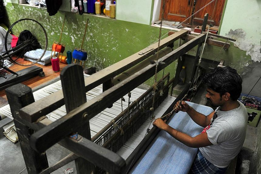 In this photograph taken on April 22, 2014 an Indian labourer weaves a sari, the traditional dress of Indian women, at a handloom factory in Rajapura Varanasi. Bosses and craftsmen say the Banarasi silk industry is hanging on by a thread and could be