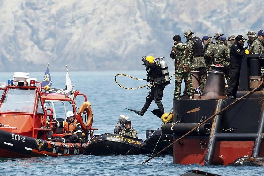 A diver jumps into the sea near an area where the capsized passenger ship Sewol sank during a rescue operation in Jindo on April 25, 2014. -- FILE PHOTO: REUTERS