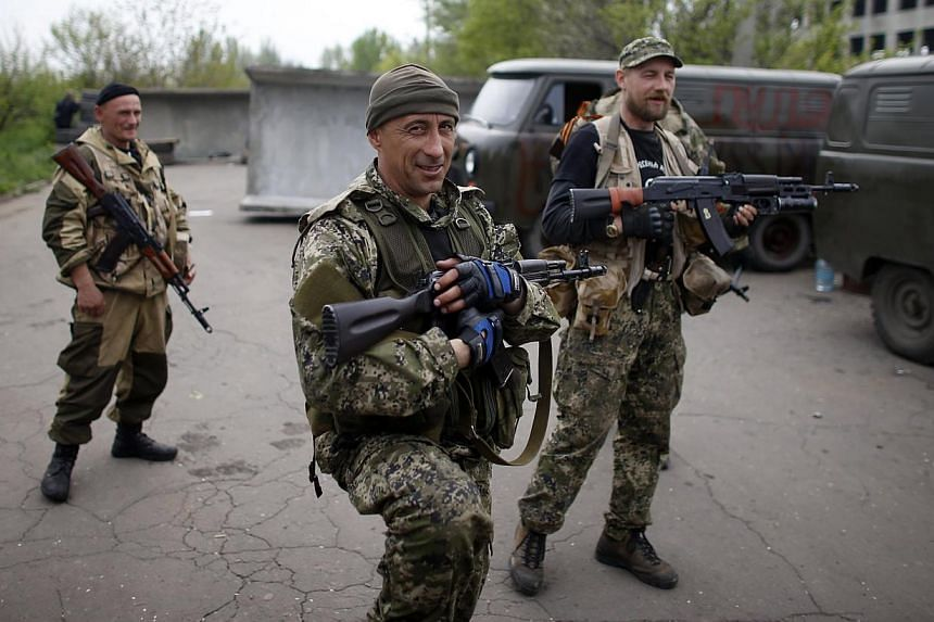 Pro-Russian rebels stand guard at a checkpoint near a Ukrainian airbase in Kramatorsk, in eastern Ukraine May 2, 2014. Pro-Kremlin rebels, who the West say are backed by Moscow, are holding more than a dozen towns and cities in east Ukraine. --