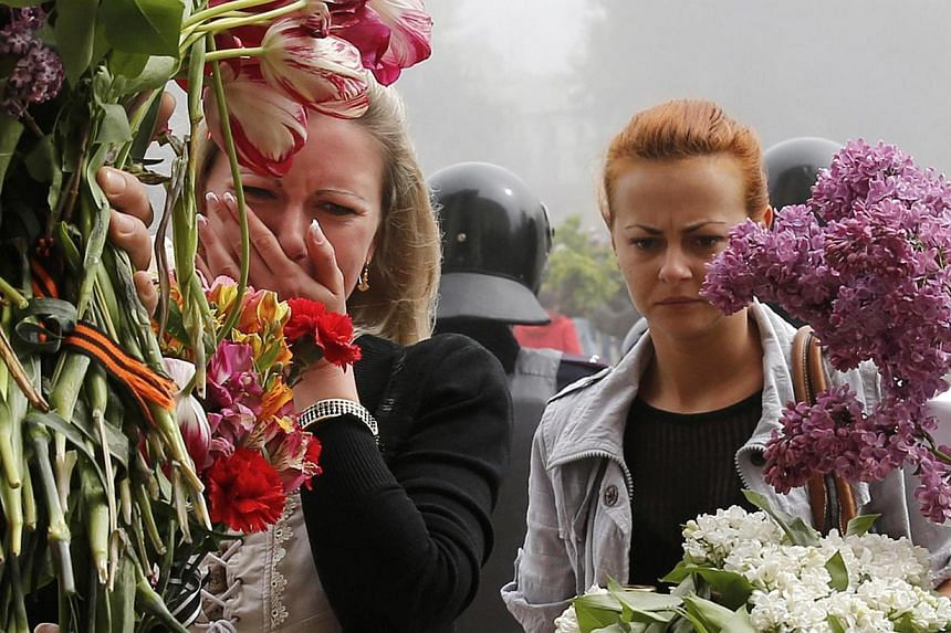 Women bring flowers in memory of people killed in recent street battles outside a trade union building, where a deadly fire occurred, in Odessa, on May 3, 2014. At least 42 people were killed in street battles between supporters and opponents of Russ