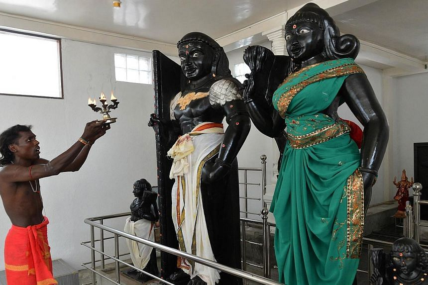 In this photograph taken on March 7, 2014 a Hindu priest holds a lit coconut oil lamp in front of statues of Prince Vijaya (centre) and demon Princess Kuveni (right) at the Sri Subramaniam temple in the southern town of Matara. At a temple in the hea