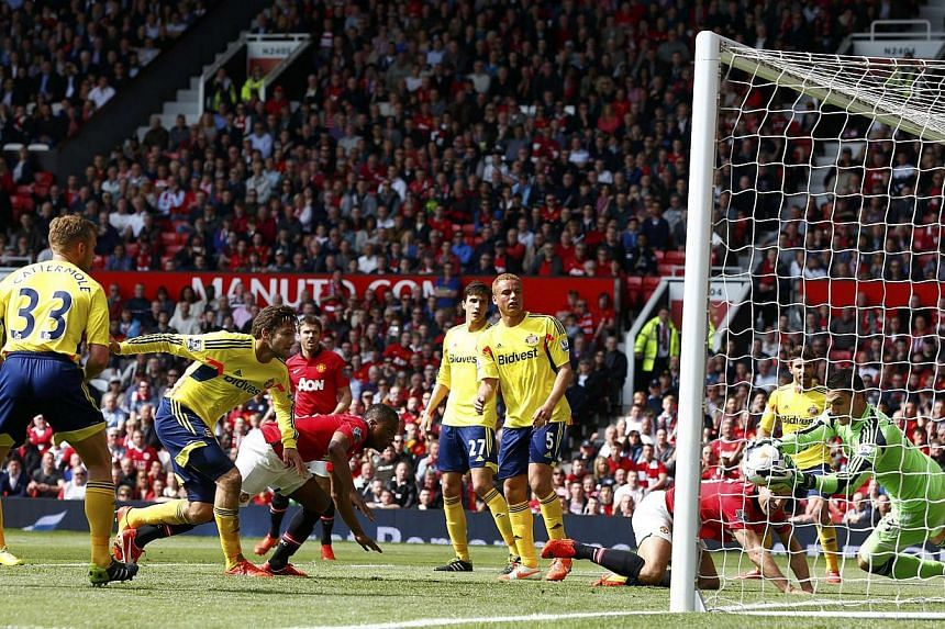 Patrice Evra (centre) of Manchester United's header is saved by Sunderland's goal keeper Vito Mannone during their English Premier League soccer match at Old Trafford in Manchester on May 3, 2014. -- PHOTO: REUTERS