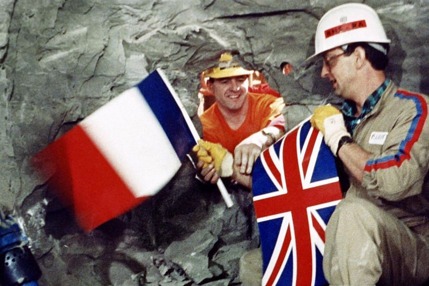 Tunnel workers Philippe Cozette from France (right) and Graham Fagg from England shake hands while holding national flags during the breakthrough in the construction of the Channel Tunnel on Dec 1, 1990. -- FILE PHOTO: AFP