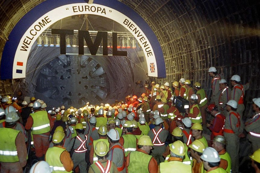 "French and British TML (TransManche Link) workers look at the Tunnel boring machine (TMD) ""Europa"" during the link-up in the North gallery of the Channel Tunnel on May 22, 1991. -- FILE PHOTO: AFP"