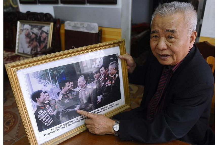This picture taken on March 27, 2014 shows 79-year-old Dien Bien Phu veteran Hoang Dang Vinh holding a photograph where he (second left) was meeting with late general Vo Nguyen Giap (centre) during an interview with AFP at his home in the northern pr