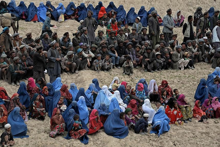 Afghan villagers affected by landslides wait to get aid supplies during a distribution in the Argo district of Badakhshan on May 4, 2014. Grief-stricken and desititute Afghan villagers vented anger on their government as they scrambled for emerg