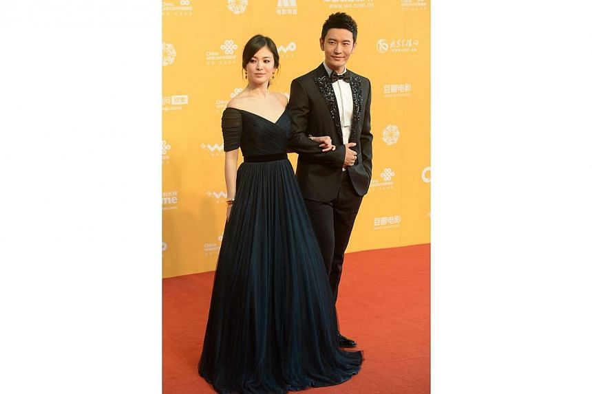 This picture taken on April 16, 2014 shows South Korean actress Song Hye Kyo (Left) and Chinese actor Huang Xiaoming posing on the red carpet at the opening ceremony of the fourth Beijing International Film Festival in Beijing. -- FILE PHOTO: AFP