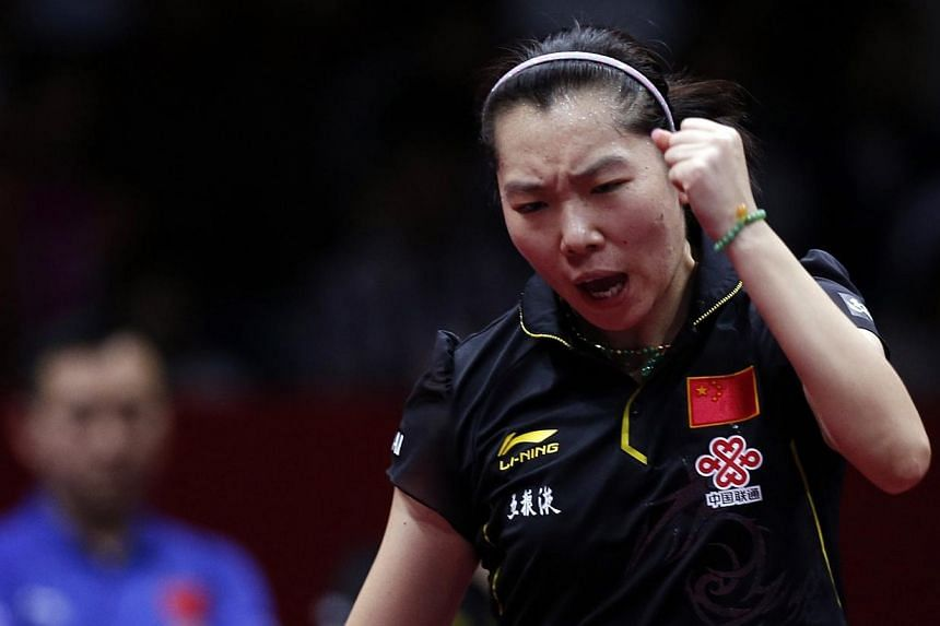 China's Li reacts after winning a point against Japan's Kasumi Ishikawa during their women's final match at the World Team Table Tennis Championships in Tokyo.China overcame the shock upset of world and Olympic champion Zhang Jike to sweep the