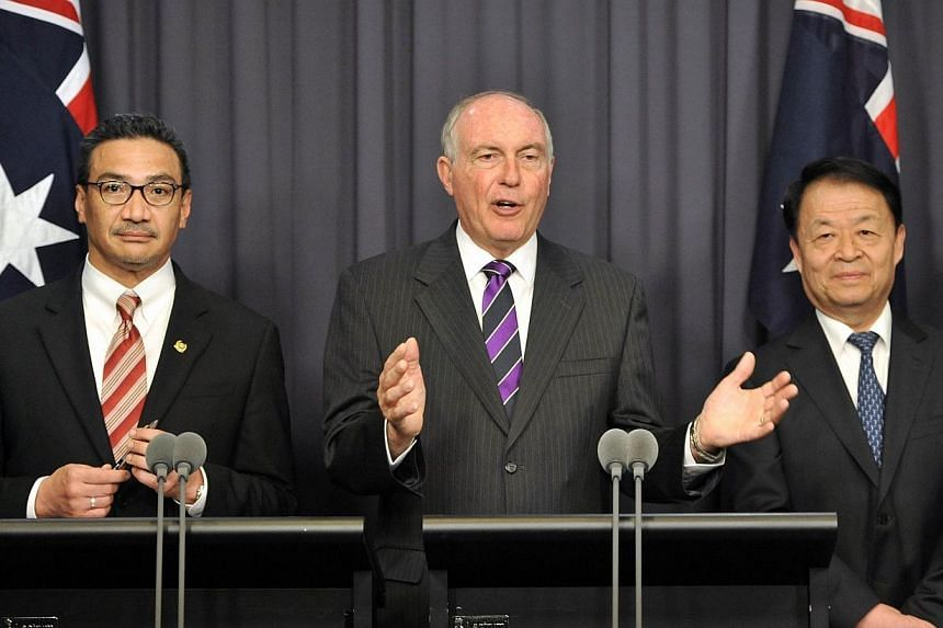 Australia's Transport Minister Warren Truss (Center) speaks during a press conference with Malaysia's Transport Minister Hishammuddin Hussein (Left) and Chinese Transport Minister Yang Chuantang (Second from Right) after talks about missing Malaysia