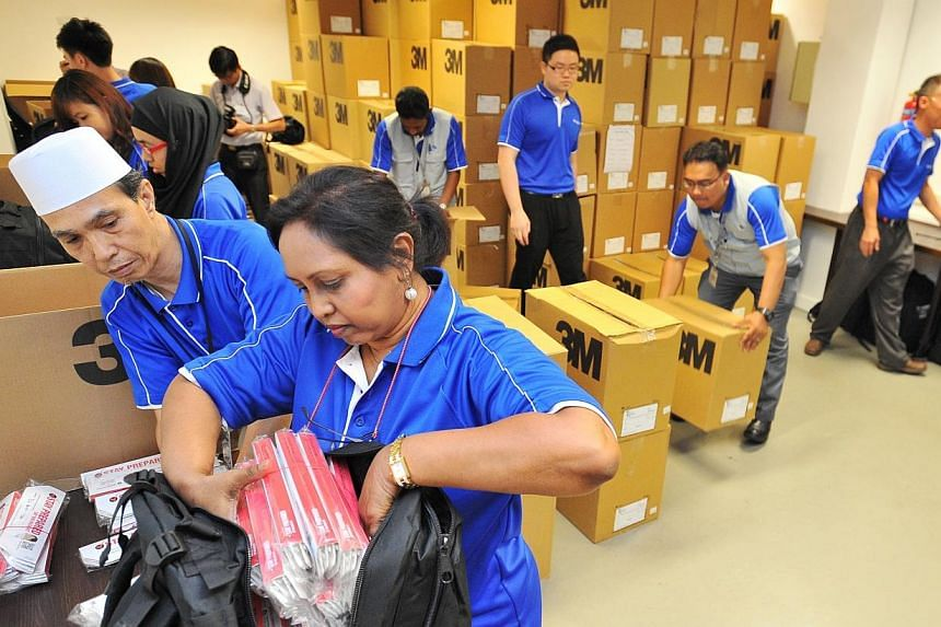 Madam Mary Ellamah Abishagam, (bottom right) 57, Senior Admin Assistant from Singapore Power, packing starter kits with Mr Mohamed Amin Bin Mohamed, (bottom left) 54, Admin Assistant from Singapore Power, at Singapore Power training institute on May