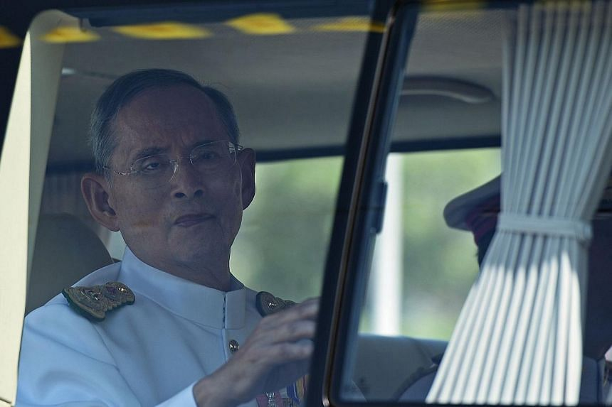 Thai King Bhumibol Adulyadej waves to a crowd of well-wishers as he travels in a motorcade to the Royal Palace to mark the 64th anniversary of his coronation in the seaside city of Hua Hin, some 200km south of Bangkok, on May 5, 2014. -- PHOTO: AFP