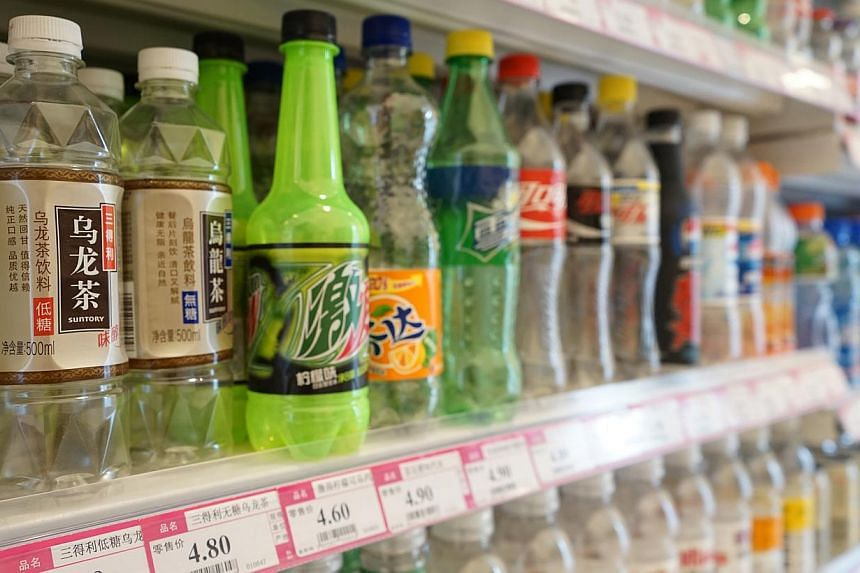 Items can be paid for at the cashier (left) at Xu Zhen's (above) ShanghART Singapore. Interactive art installation ShanghART Supermarket (right) resembles a convenience store in China and is stocked with sealed empty items such as bottles of beverage