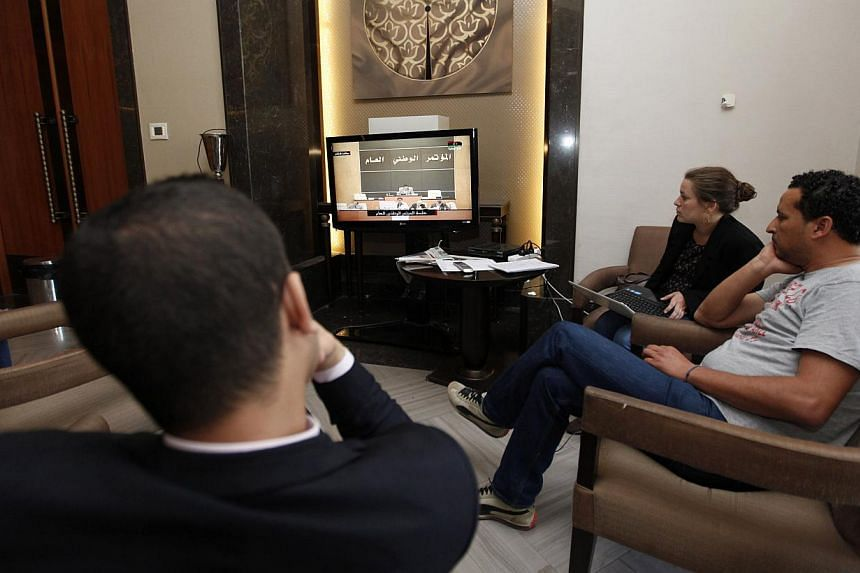 Reporters watch a live feed of Libyan members of parliament meeting to decide on the new prime minister at the parliament in Tripoli on May 4, 2014. -- PHOTO: REUTERS