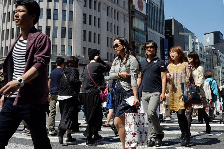 Pedestrians walk in Tokyo's Ginza shopping district on May 2, 2014.A strong 6.0-magnitude earthquake shook buildings in Tokyo early Monday, seismologists and AFP reporters said, but officials stressed there was no risk of a tsunami. -- FILE PHO