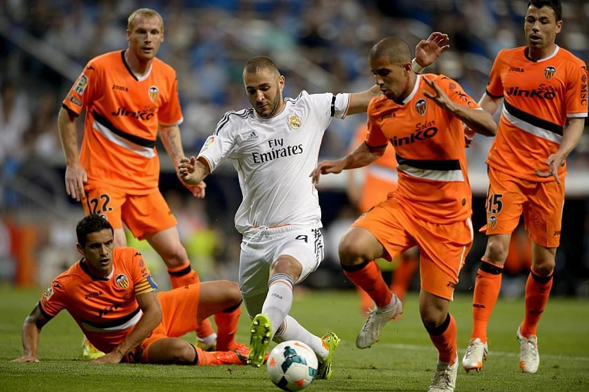 Real Madrid's French forward Karim Benzema (centre) vies with Valencia's French midfielder Sofiane Feghouli during the Spanish league football match Real Madrid CF vs Valencia CF at the Santiago Bernabeu stadium in Madrid on May 4, 2014. -- PHOTO: AF