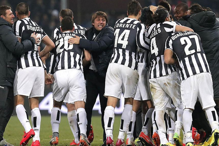 Juventus' coach Antonio Conte celebrates with players at the end of the Italian Serie A football match Genoa Vs Juventus on March 16, 2014 at Luigi Ferraris Stadium in Genoa. -- PHOTO: AFP