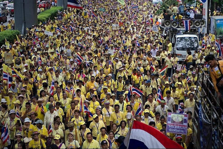 Anti-government protesters march to mark the 64th anniversary of Thai King Bhumibol Adulyadej's coronation, in Bangkok on May 5, 2014. Thailand's revered King Bhumibol Adulyadej made a rare public appearance on May 5 to mark the 64th anniversary of h