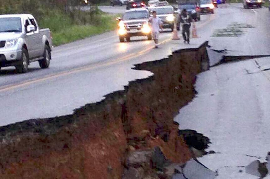 Thai motorists drive next to a large crack on the road caused by the earthquake on a highway in Chiang Rai province, northern Thailand, on 05 May 2014. A strong magnitude-6 earthquake centered in Phan district in the province of Chiang Rai shook nort