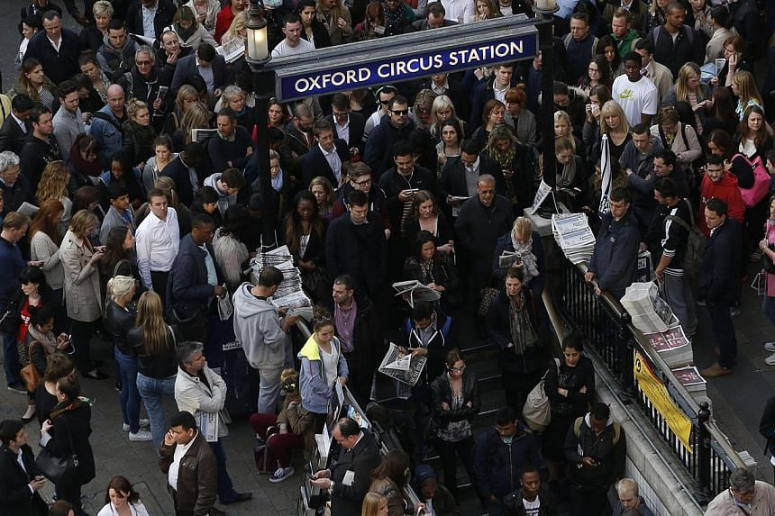 Commuters and shoppers queue for access to Oxford Circus underground station, one of the open tube stations, during strikes in London on April 29, 2014. -- FILE PHOTO: REUTERS