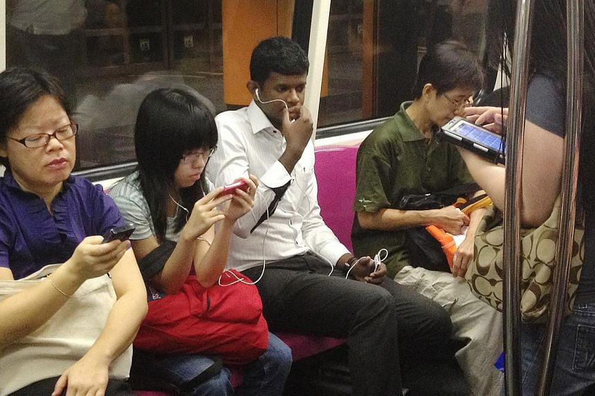 MRT commuters using their mobile devices. Fewer people are buying tablet mobile devices these days as they turn to bigger-screen smartphones for their communication and entertainment needs. -- ST FILE PHOTO: TED CHEN
