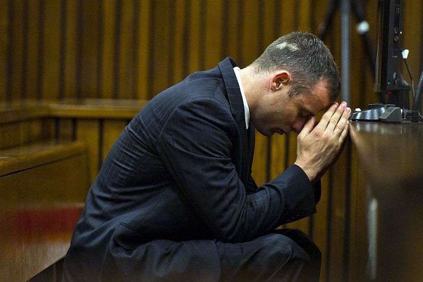South African Paralympian Oscar Pistorius is seen in the dock on April 17, 2014 at the North Guteng High Court in Pretoria. The athlete's murder trial will resume today after a two-week postponement. -- FILE PHOTO: AFP