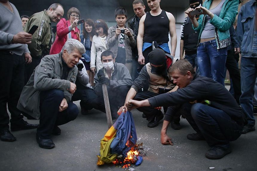 Pro-Russia protesters burn a Ukranian flag outside the district council building in Donetsk, eastern Ukraine on May 4, 2014. -- PHOTO: REUTERS
