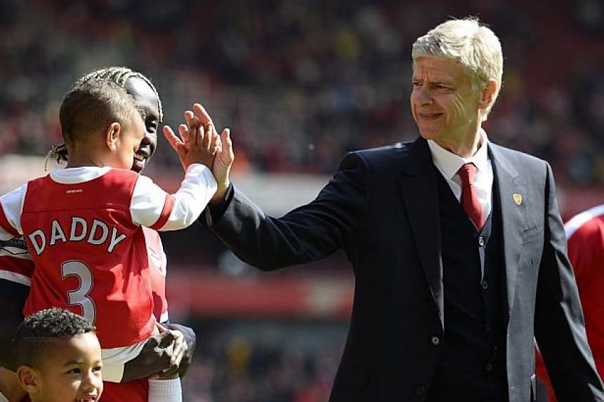 Arsenal manager Arsene Wenger (right) greets Bacary Sagna's children as they walk around the pitch after their English Premier League football match against West Bromwich Albion at the Emirates stadium in London May 4, 2014. -- PHOTO: REUTERS