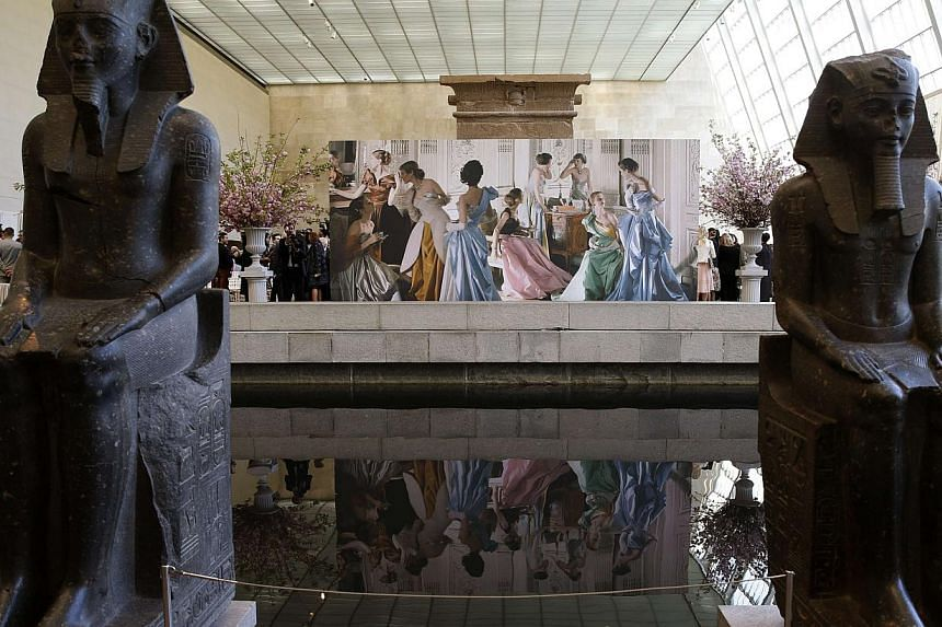 Egyptian sculptures are seen at the Metropolitan Museum of Art along with a mural celebrating the opening of the Anna Wintour Costume Center at the Costume Institute at the Metropolitan Museum in New York on May 5, 2014. -- PHOTO: REUTERS