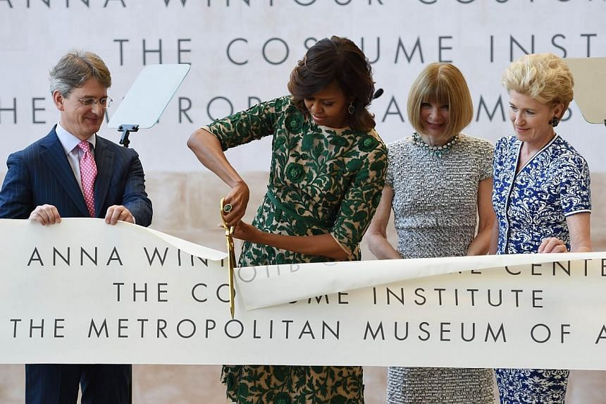 US First Lady Michelle Obama (2nd left) cuts the ribbon officially opening The Costume Institute's new Anna Wintour Costume Center at The Metropolitan Museum of Art on May 5, 2014 in New York. -- PHOTO: AFP
