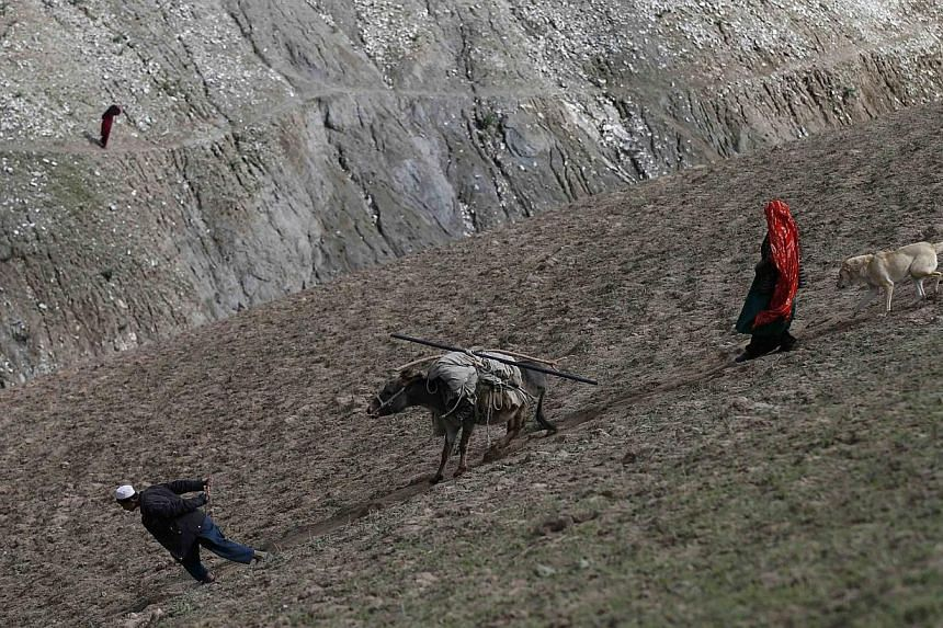 Afghans carry their aid on a donkey near the site of a landslide at the Argo district in Badakhshan province.As many as 2,700 people may be buried after a landslide in the Ab-e-Barak village in Badakhshan province in Afghanistan on May 2. -- PH