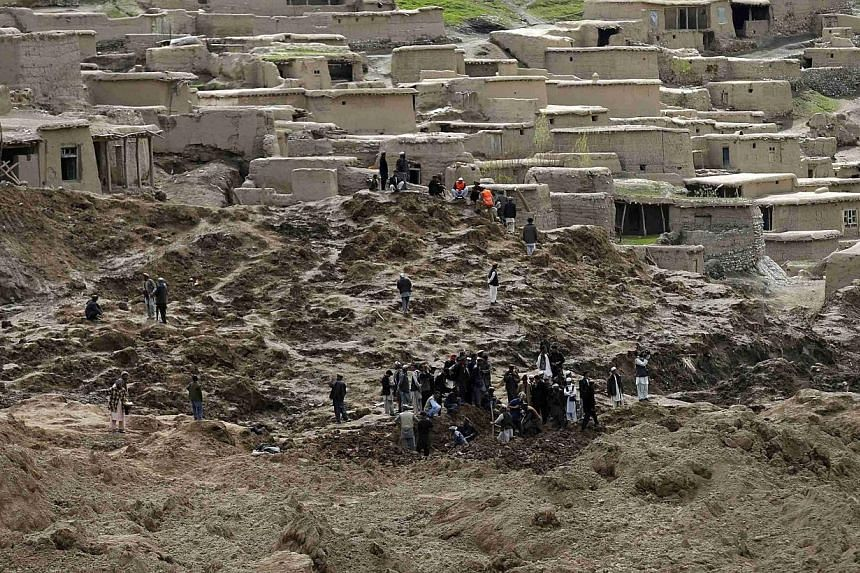 Afghan villagers search for dead bodies at the site of a landslide at the Argo district in Badakhshan province on May 5, 2014.As many as 2,700 people may be buried after a landslide in the Ab-e-Barak village in Badakhshan province in Afghanista