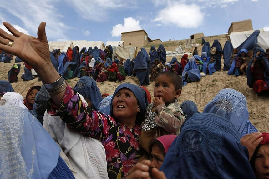 Displaced Afghans wait for aid near the site of a landslide at the Argo district in Badakhshan province May 5, 2014.As many as 2,700 people may be buried after a landslide in the Ab-e-Barak village in Badakhshan province in Afghanistan on May 2