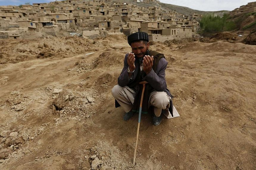 Afghan survivor prays at the site of a landslide that occurred on Friday at the Argo district in Badakhshan province on May 5, 2014.As many as 2,700 people may be buried after a landslide in the Ab-e-Barak village in Badakhshan province in Afgh