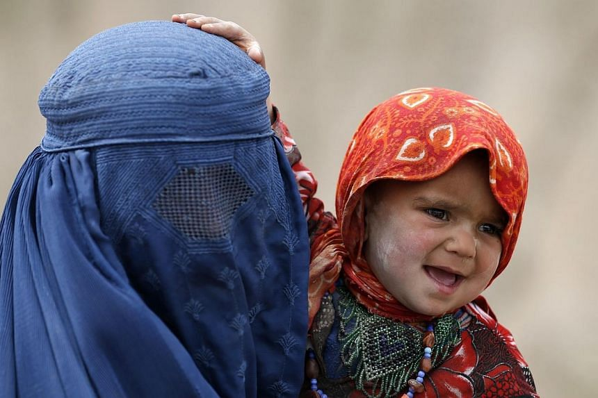 An Afghan woman holds her child as she waits for aid near the site of a landslide at the Argo district in Badakhshan province.As many as 2,700 people may be buried after a landslide in the Ab-e-Barak village in Badakhshan province in Afghanista